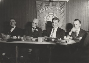 four men formally dressed sitting at a table facing the camera