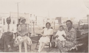 Charlie Krempeaux and Family sitting outside on the main street of The Pas likely during the warmer months.
