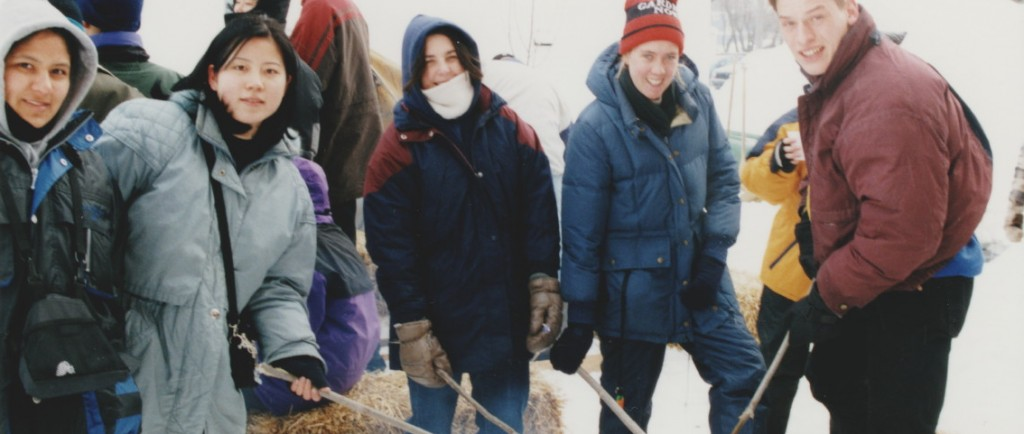A number of young people dressed in winter gear roasting bannock over a fire. The activity was part of the 1999 Trappers' Festival.