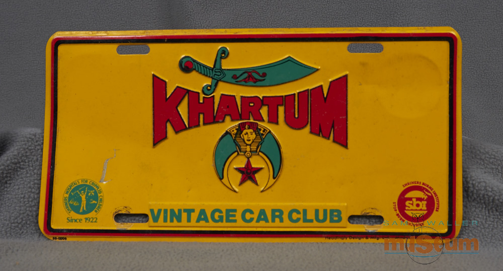 Golden yellow licence plate with red and green lettering and symbols of the Shriners club which consists of an upside down quarter moon filled in with green colouring, an Egyptian Pharaoh inside a pyramid at the top of the moon and a star hanging underneath the Pharaoh.
