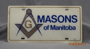Plain white licence plate with blue lettering for the Masons of Manitoba and a gold symbol lined in blue.