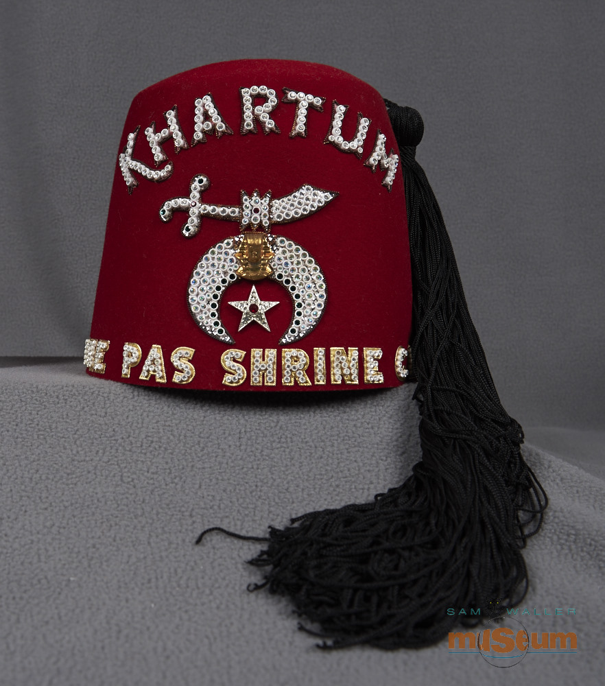 A red Shriners fez. On top there are four sets of air holes in the form of circles, and three rows of holes in each circle. The beaded lettering on the front reads