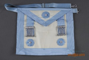 White apron with a blue border and strap that looks like an over-the-shoulder book bag. A flap, triangular in shape, hangs down 1/3 of the way centered by a silver mason badge with a blue floral design around it. The back is a piece of blue cotton fabric and the front is a white leather-material with blue bordering around the edges and front flap. Two blue cloth strips hang down with a metallic bar (silver) and 7 chains and small metal globes hanging from each bar on the bottom left and right corners are silver metal mason badges. In belt fastener is an