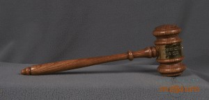 This gavel has a handle attached to a mallet style head, both made of wood and lightly stained with a varnish layer. Both parts are carved with simple lathe style designs. The middle of the mallet head is wrapped with a sheet of metal and the ends are fixed where the handle attaches to the mallet head. The metal sheet has the Lions emblem and the text: