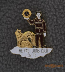 """The gold pin highlights a trapper holding a Lions emblem in his hand. He has a white face and hands, a black hat and brown clothing. To his right is a sled dog, completely in gold. They are both standing on an irregular patch of white snow. The gold text """"The Pas Lions Club/5M-13"""" appears in the in the snow patch. The text """"Artiss-Regina/Taiwan"""" appears near the bottom of the textured gold back. This pin is cut to the shape of the Trapper, sled dog and snow patch and has a single butterfly clutch."""