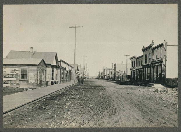 1880s Photo of Stephen Avenue - the original Lougheed home is the second building on the left with the bay window.