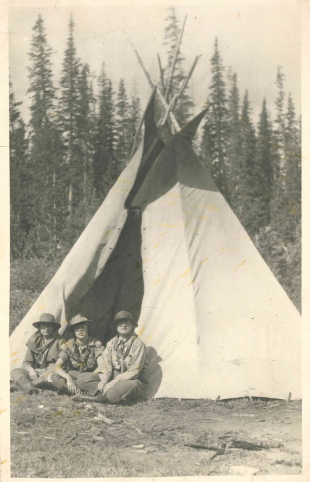 Photo of Dorothy Lougheed in between 2 other girls all dressed in scout clothes in front of a teepee.