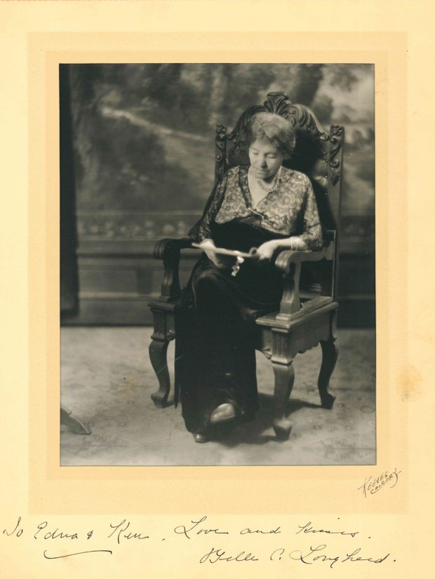 Studio photo of Belle as elderly woman seated in a chair reading.