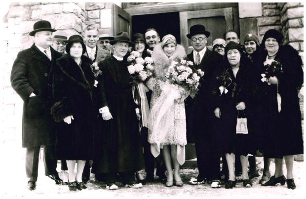 Group photo from Clarence Lougheed's wedding in front of a church door in Banff, Isabella stands in front row next to Clarence.