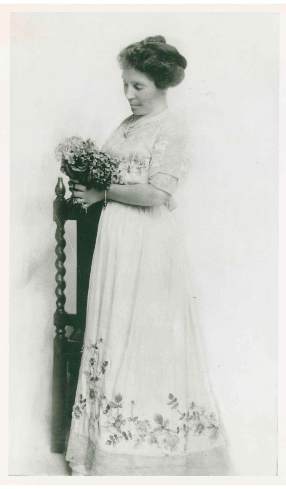Photo of Belle Lougheed holding bouquet of flowers