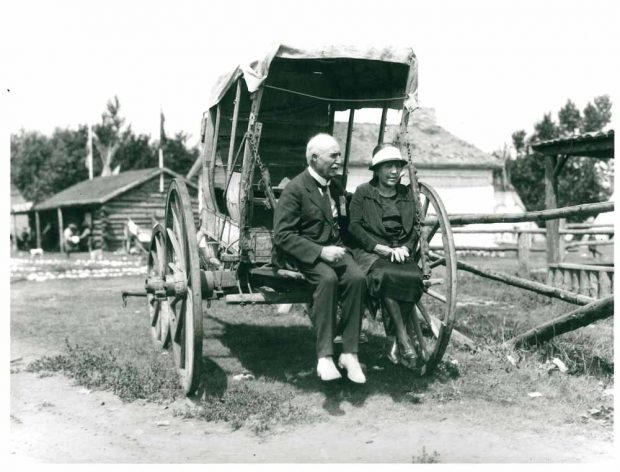 Belle and J.J. McHugh seated on the back of an old covered wagon at the Stampede in 1925