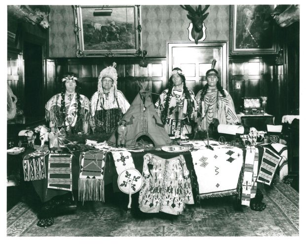 Interior shot at Beaulieu with 4 people dressed in Indigenous clothing behind a table with Indigenous objects; Southern Alberta Pioneer and Oldtimers Women's group in 1923