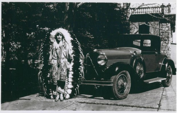 Photo of Dorothy Lougheed in large feathered headdress beside car at Beaulieu