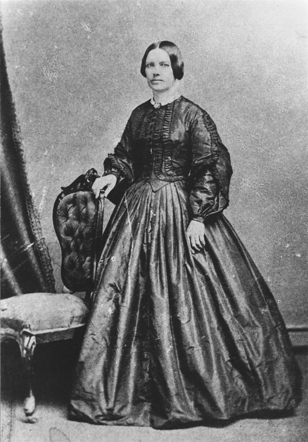 Photo of Lady Strathcona (Isabella Sophia Hardisty) standing beside a chair wearing a formal dress