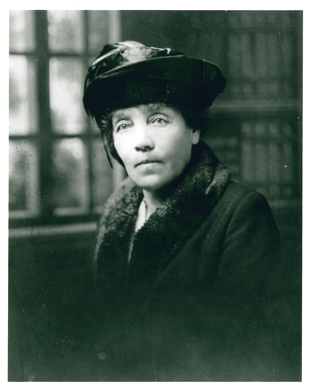 A portrait of Belle Lougheed in hat and winter coat with fur collar.