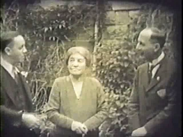 A period photograph of two well dressed men and a woman in a garden