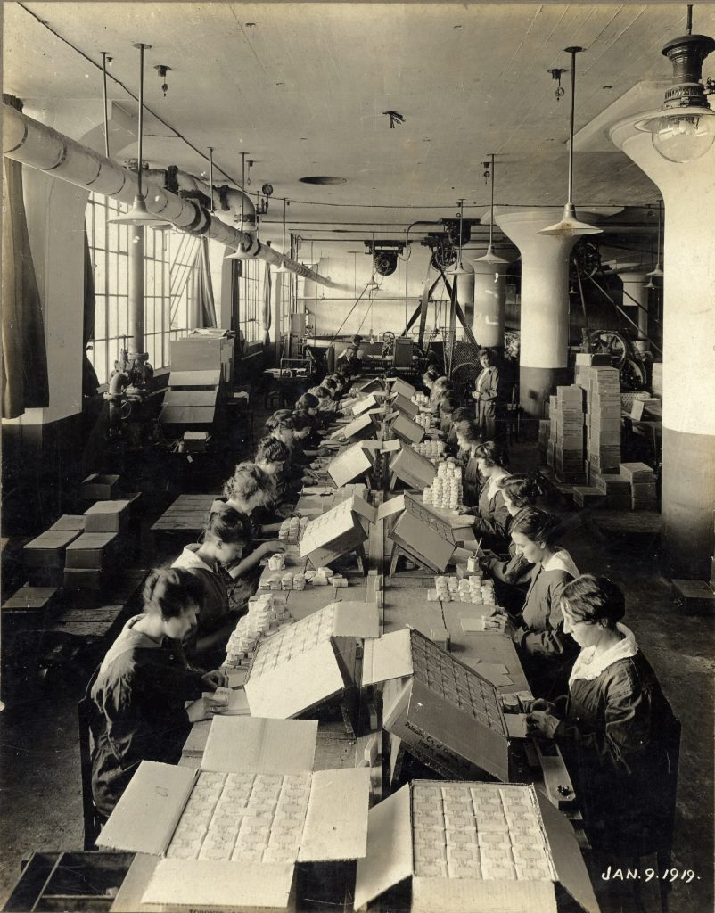 Deux rangées de femmes travaillent à une longue table dans un entrepôt dans une photo en noir et blanc. Des boîtes et équipements d'usine se trouvent en toile de fond.