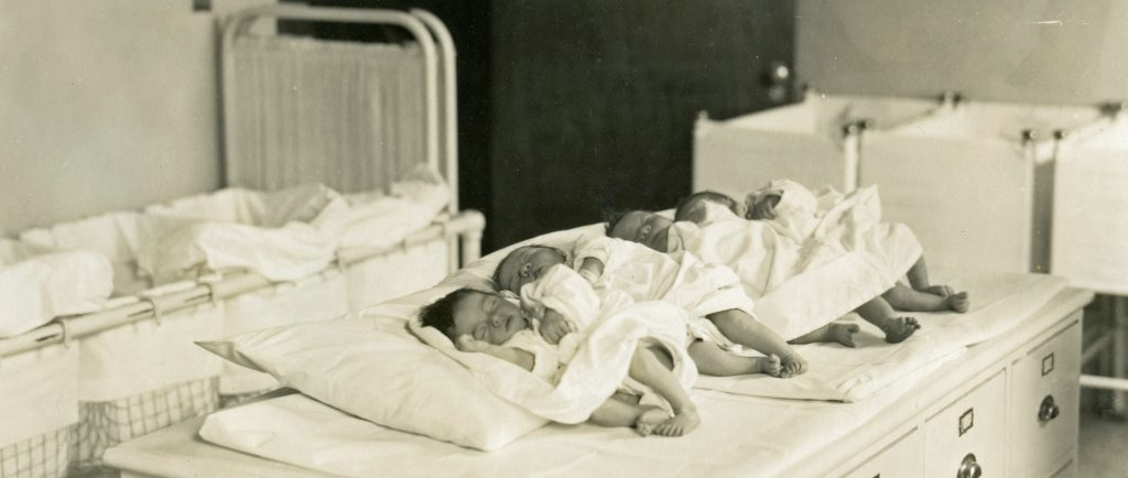 Sleeping newborn babies lined up in a row on a table with cribs in the background in a black and white photo.