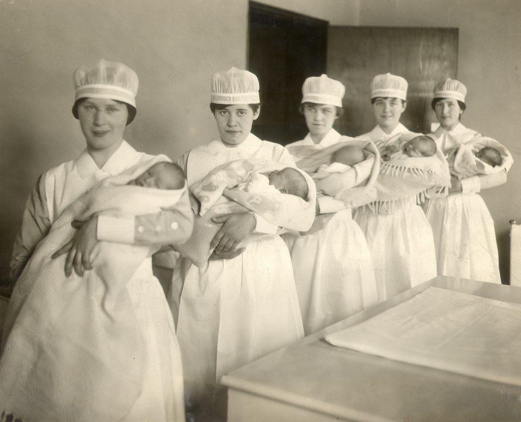 Cinq infirmières en uniforme tiennent des bébés enveloppés à côté d'une grande table dans une photo en noir et blanc.