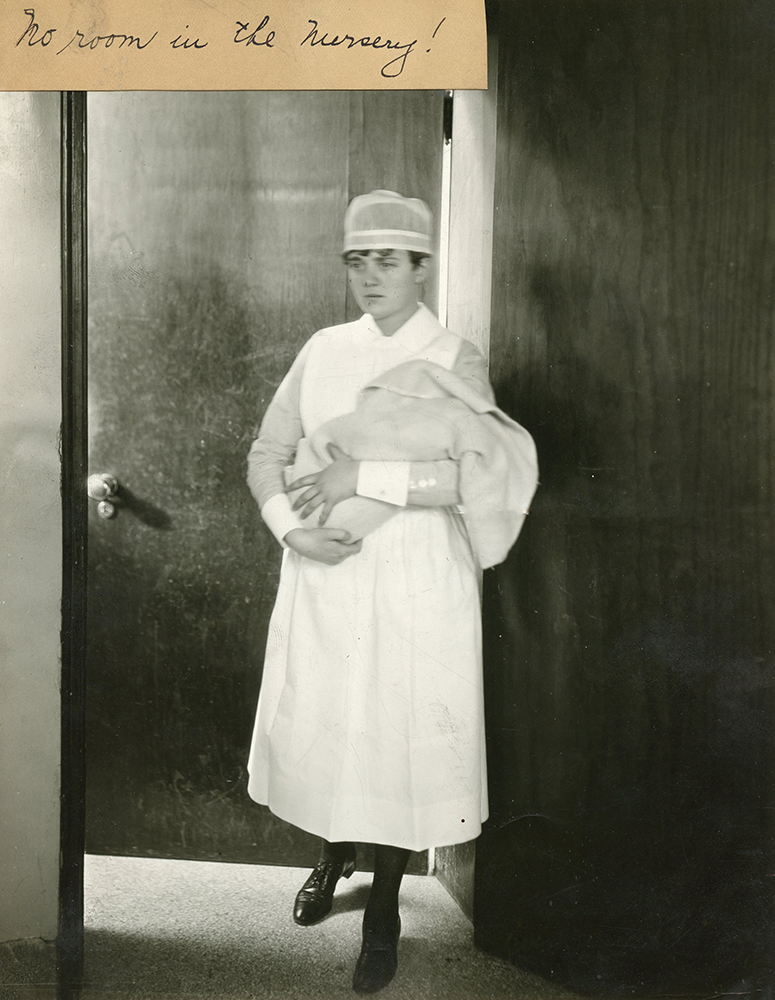 A nurse in uniform holds a newborn wrapped in a blanket as she exits a room in a black and white photo.