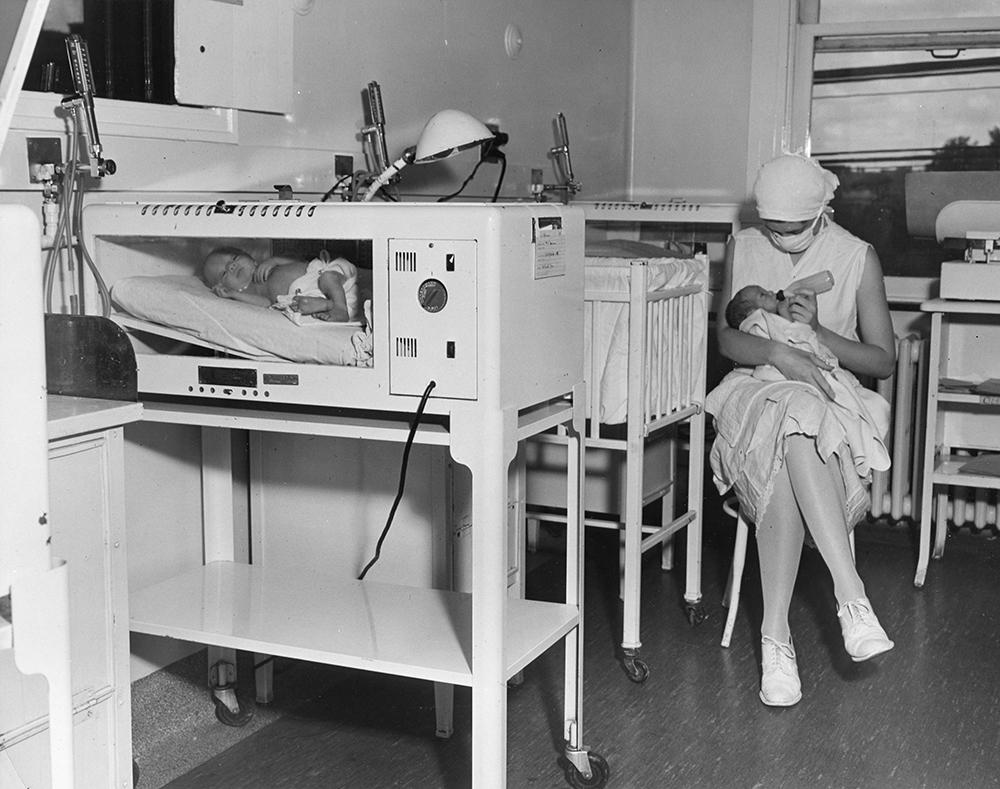 Une infirmière masquée nourrit un bébé assise sur une chaise à côté du lit de bébé dans une photo en noir et blanc. Un deuxième bébé se trouve dans un incubateur à l'avant-plan gauche.