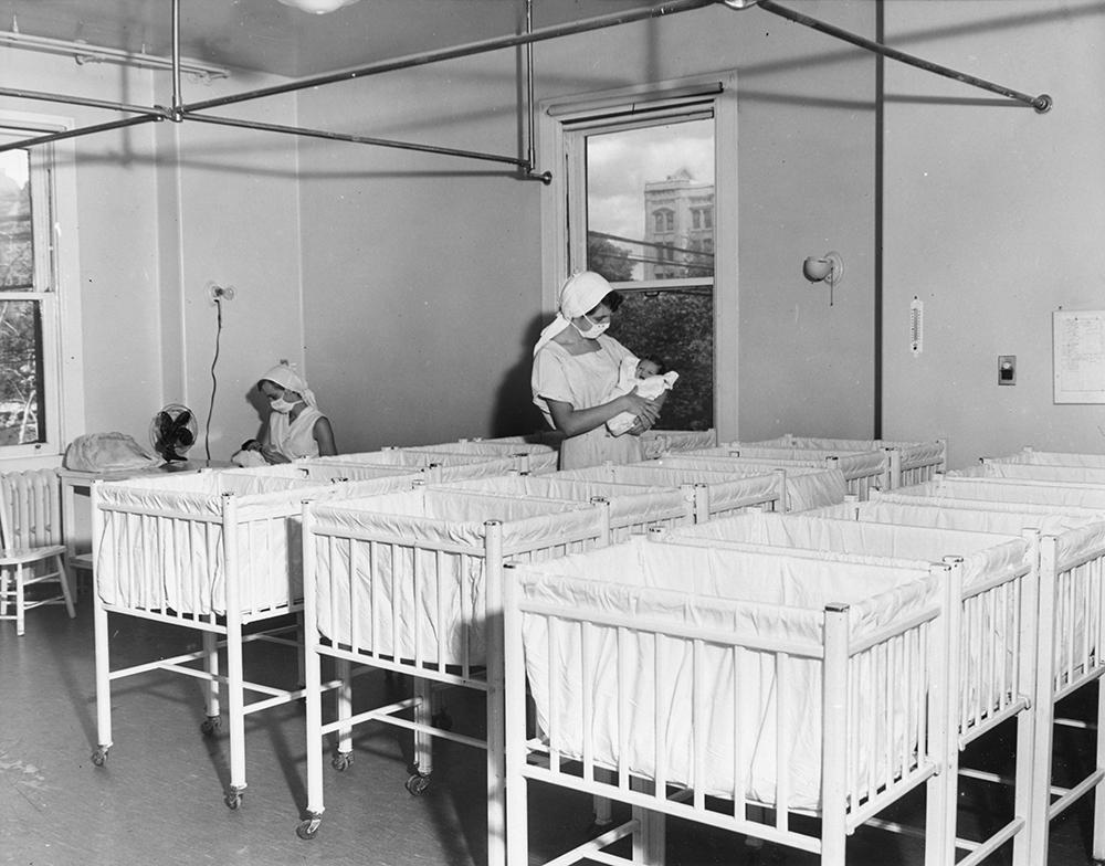 Deux infirmières portant des masques dans une pouponnière pleine de lits de bébé blancs dans une photo en noir et blanc. Chacune tient un nouveau-né.
