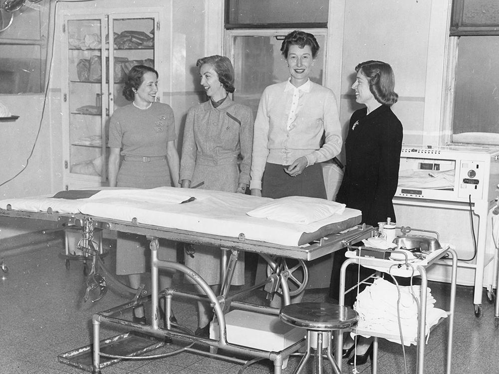 Quatre femmes habillées de vêtements de tous les jours se tiennent derrière une civière dans une salle avec de l'équipement médical dans une photo en noir et blanc.