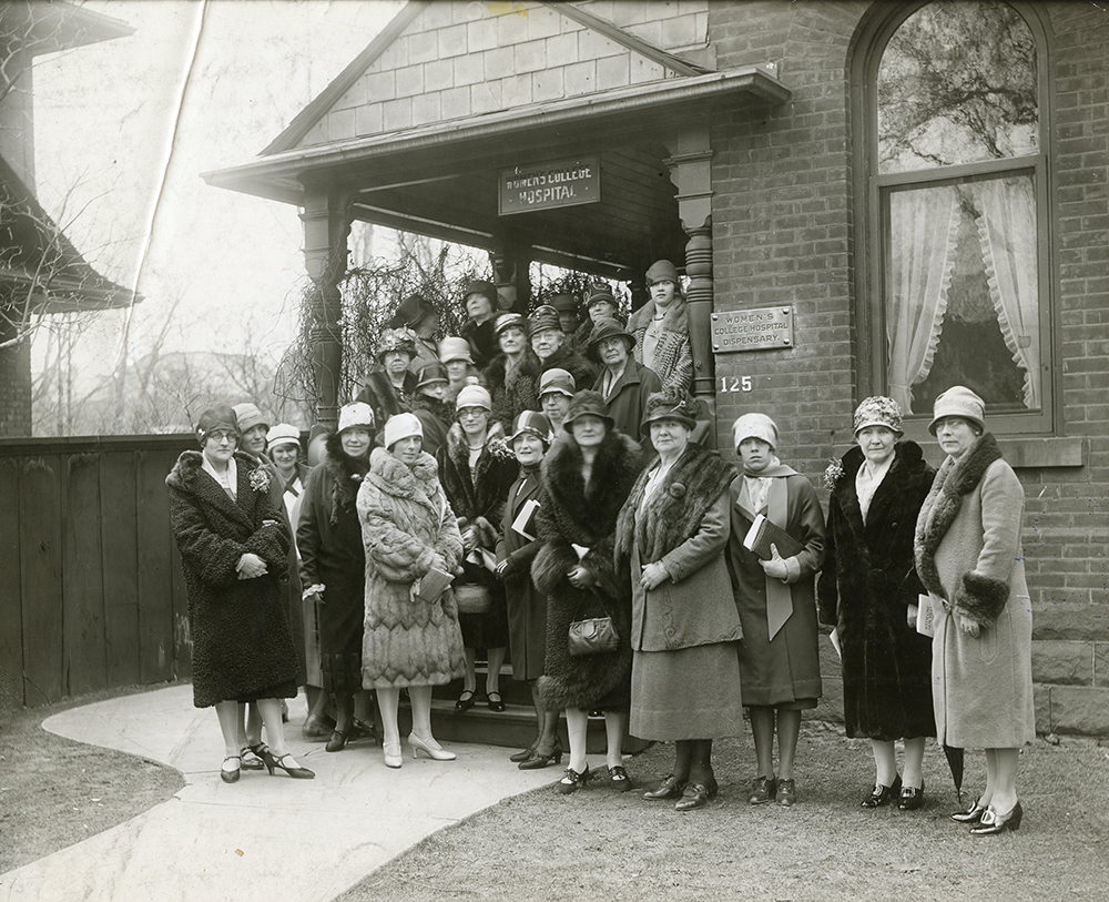 Un groupe de femmes habillées de manteaux d'hiver et de chapeaux à la mode à l'extérieur du Women's College Hospital dans une photo en noir et blanc.