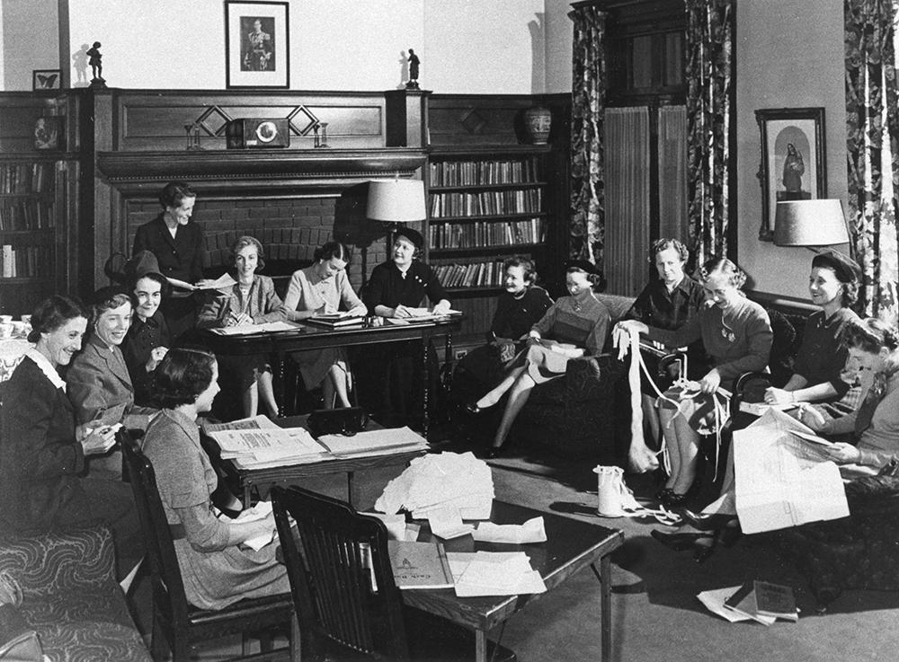 Des femmes assises dans un salon travaillent sur des documents et des tricots dans une photo en noir et blanc. Des tables ont été arrangées près des divans pour la réunion.