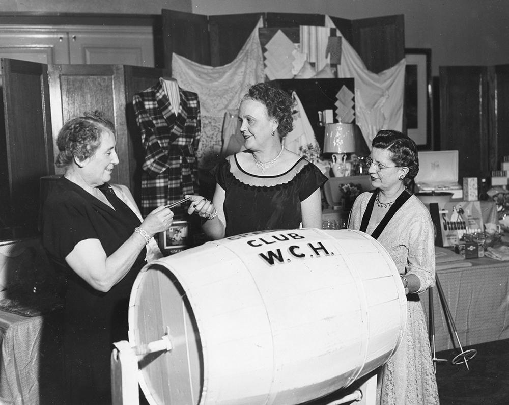 Trois femmes puisent un billet dans un baril étiqueté Cradle Club W.C.H. dans une photo en noir et blanc. Les objets à gagner sont étalés sur une table derrière elles.