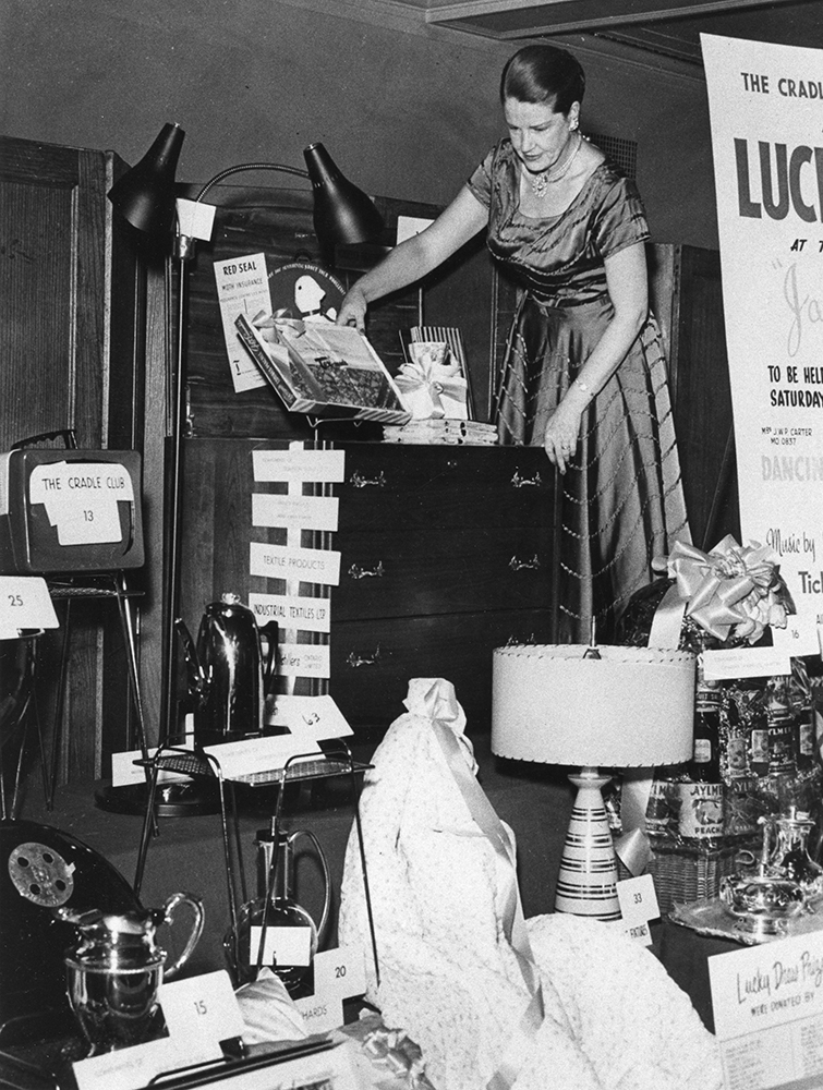 A woman in formal wear arranges domestic goods on a stage in a black and white photo.