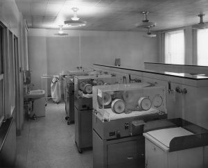 Une photo en noir et blanc d'un salle avec une rangée de trois incubateurs contenant des bébés. Un poste à langer se trouve à l'avant-plan et un lavabo à gauche.