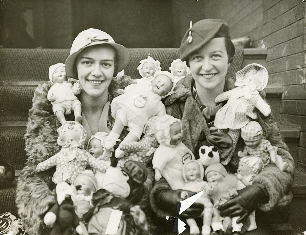 Two fashionably dressed women with arms full of baby dolls sitting on outdoor steps in a black and white photo.