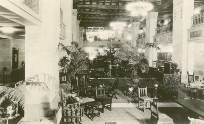 Hall d'entrée élégamment décoré avec choix de sièges divers, palmiers en pots et lustres dans une photo en noir et blanc.
