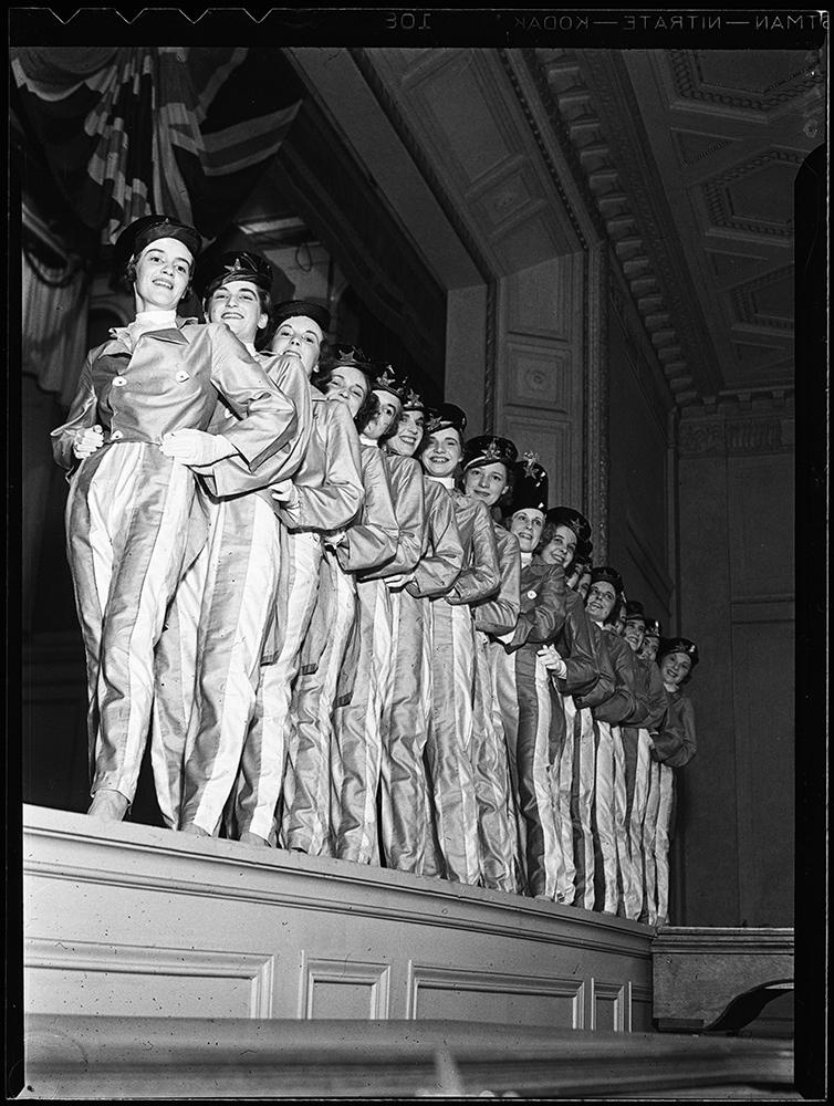 Des femmes en costumes de fanfare identiques posent en rangée sur une scène dans une photo en noir et blanc.
