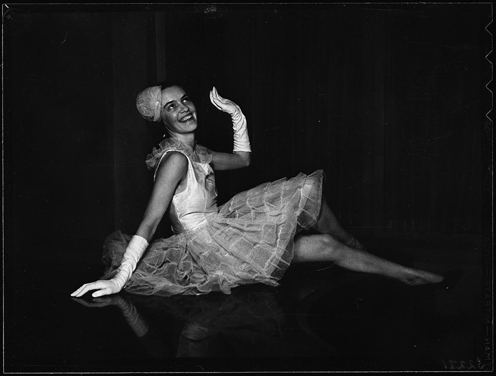 Peggy Beal assise à terre pose en tutu et gants dans une photo en noir et blanc.