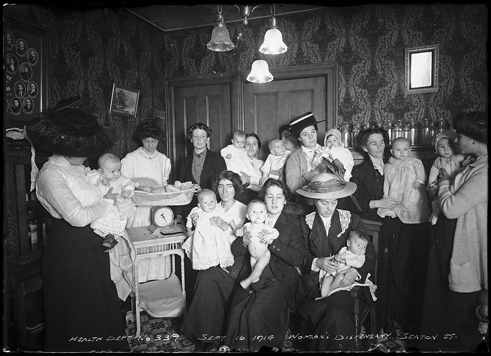 Un grand groupe de mères tenant leurs bébés posent dans un salon dans une photo en noir et blanc. Une infirmière pèse un bébé à gauche.