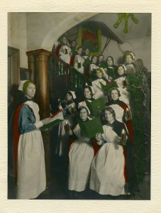 Nurses holding candles and carol books are lined up on the stairs in an old photo. One nurse leads them while another plays violin.