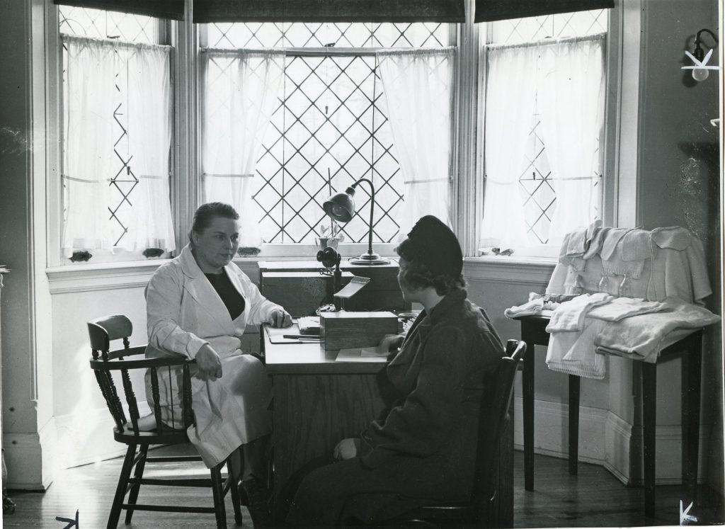 Un professionnel médical en consultation avec une femme à son bureau situé devant une fenêtre en baie dans une photo en noir et blanc. Des linges de bébé et vêtements tricotés sont étalés sur une petite table à droite.
