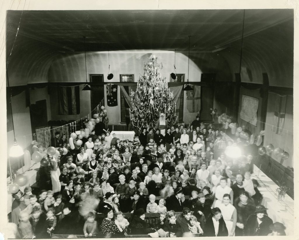 Women, children and nurses gather around long tables in a black and white photo. Balloons are hung and Santa stands before a large Christmas tree at the back of the room.