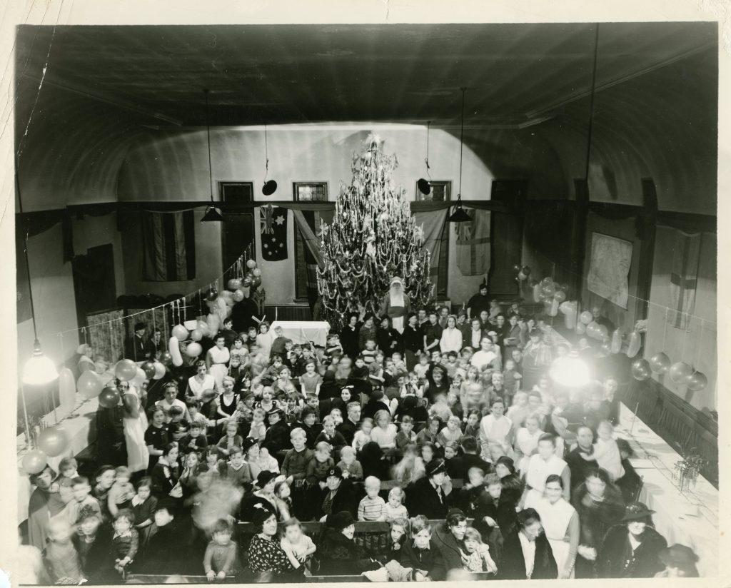 Femmes, enfants et infirmières rassemblés autour de tables longues dans une photo en noir et blanc. Des ballons sont suspendus et le Père Noël se tient près du grand sapin au fond de la salle.