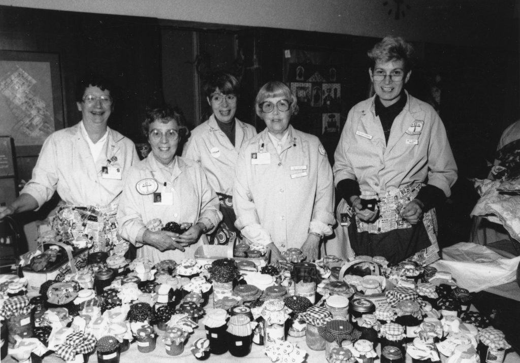 Des femmes en pardessus identiques se tiennent devant une table couverte de fruits en conserve dans une photo en noir et blanc.