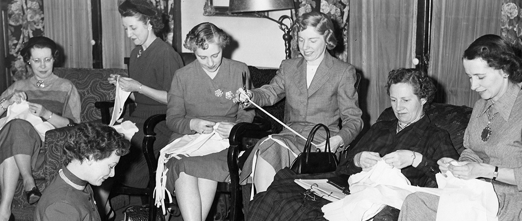 Women work on individual sewing projects in a black and white photo. Chairs have been added to the room to accommodate them. One woman sits on the floor in the left corner.