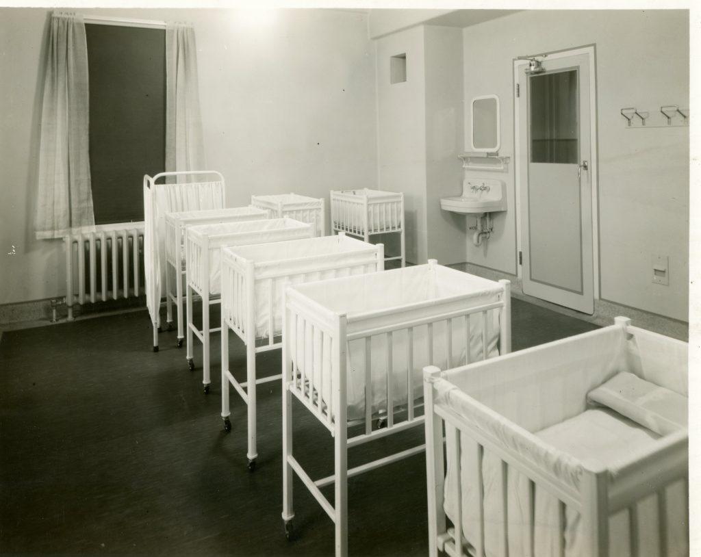 Lits de bébé nombreux dans une pièce claire et ouverte dans un hôpital, avec lavabo et miroir dans le coin près de la porte dans une photo en noir et blanc.