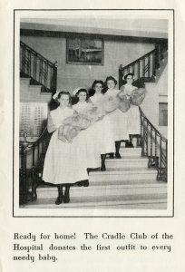 Cinq jeunes infirmières posent sur un escalier tenant fièrement des bébés portant des chapeaux et enveloppés de couvertures dans une photo en noir et blanc.