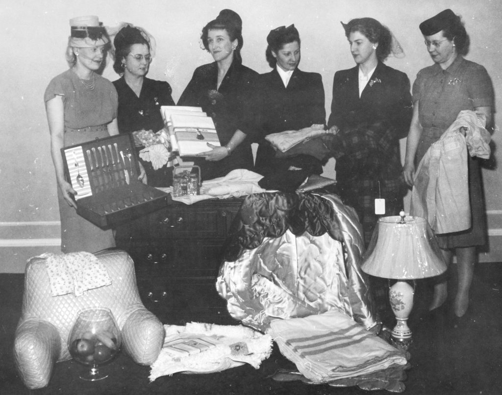 Six women in formal wear stand behind an arrangement of domestic goods in a black and white photo.