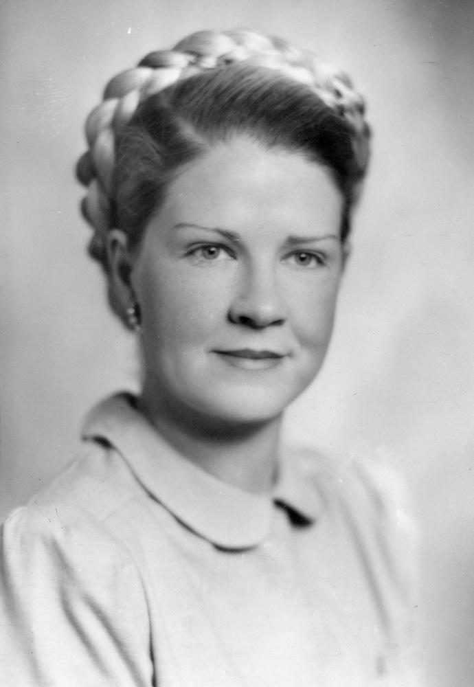 Portrait noir et blanc d'une femme souriant délicatement avec chignon tressé.