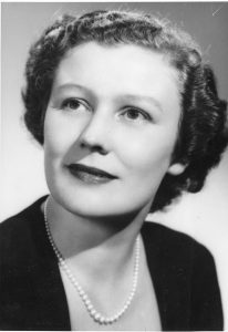 A black and white portrait of a delicately smiling woman wearing pearls.