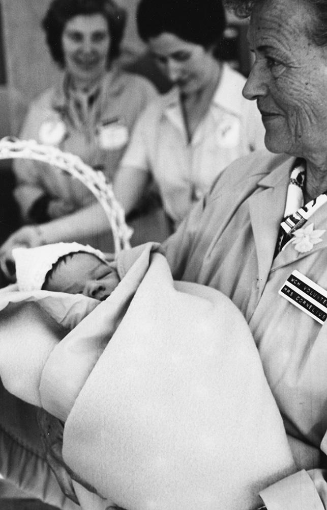 Dans une photo en noir et blanc, une femme en manteau de bénévole tient un bébé endormi enveloppé d'une couverture; deux autres femmes se trouvent en toile de fond.