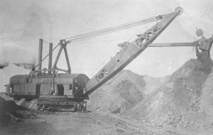 A steam shovel moves earth while building the Eastern Railway